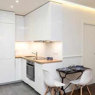 Design ideas for a scandinavian l-shaped open plan kitchen in Paris with a single-bowl sink, beaded inset cabinets, wood benchtops, white splashback, glass tile splashback, stainless steel appliances, cement tiles and grey floor.