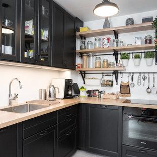 Cette image montre une cuisine nordique en L fermée avec un évier 1 bac, un placard avec porte à panneau encastré, des portes de placard noires, un plan de travail en bois, une crédence blanche, un électroménager noir, aucun îlot, un sol gris et un plan de travail beige.
