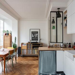 Exemple d'une cuisine américaine scandinave en L avec un évier de ferme, un placard à porte plane, des portes de placard blanches, un plan de travail en bois, une crédence blanche, un sol en bois brun, une péninsule et un plan de travail beige.