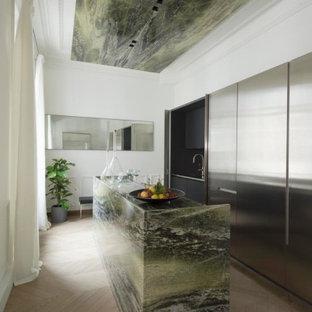 Cette image montre une cuisine design avec un placard à porte plane, une façade en inox, un sol en bois clair, un îlot central, un sol beige et un plan de travail multicolore.