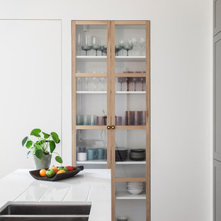 This is an example of a scandinavian galley kitchen in Paris with an integrated sink, grey cabinets, quartzite benchtops, white splashback, panelled appliances, light hardwood floors, with island, white benchtop and glass-front cabinets.