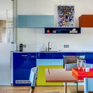 Aménagement d'une cuisine américaine linéaire contemporaine de taille moyenne avec un placard à porte plane, un sol en bois clair, des portes de placard bleues et aucun îlot.