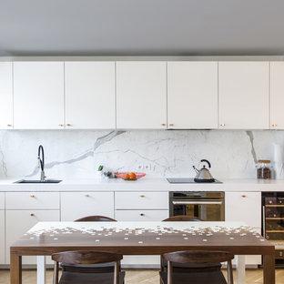 Aménagement d'une cuisine américaine linéaire contemporaine avec un évier encastré, un placard à porte plane, des portes de placard blanches, une crédence blanche, une crédence en dalle de pierre, un sol en bois clair et un plan de travail blanc.