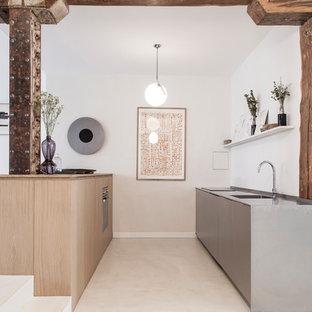 Cette image montre une cuisine parallèle design avec un évier intégré, un placard à porte plane, des portes de placard grises, un îlot central, un sol gris et un plan de travail gris.