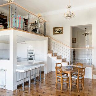 Cette photo montre une cuisine ouverte tendance en U avec un placard à porte plane, des portes de placard blanches, un électroménager blanc, un sol en bois brun, une péninsule, un sol marron et un plan de travail blanc.
