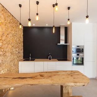 Exemple d'une cuisine ouverte linéaire montagne avec un placard à porte plane, des portes de placard blanches, un plan de travail en bois, une crédence noire, un électroménager en acier inoxydable, béton au sol, aucun îlot et un sol gris.