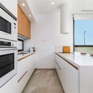 Imagen de cocina de galera, contemporánea, de tamaño medio, con fregadero de un seno, armarios con paneles lisos, puertas de armario blancas, salpicadero de vidrio, península, suelo beige y encimeras blancas