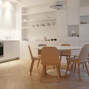 Idées déco pour une cuisine américaine linéaire scandinave de taille moyenne avec des portes de placard blanches, un sol en bois clair et aucun îlot.