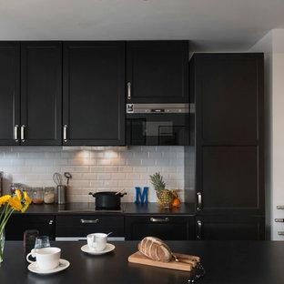 パリの中サイズのインダストリアルスタイルのおしゃれなキッチン (一体型シンク、フラットパネル扉のキャビネット、黒いキャビネット、大理石カウンター、白いキッチンパネル、ボーダータイルのキッチンパネル、黒い調理設備、セメントタイルの床、グレーの床) の写真