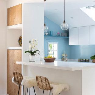 Cette photo montre une cuisine bord de mer avec un placard à porte plane, des portes de placard blanches, une crédence bleue, une péninsule, un plan de travail blanc et un sol en bois clair.