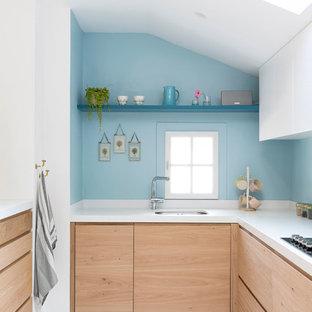 Réalisation d'une cuisine marine en L avec un évier encastré, un placard à porte plane, des portes de placard en bois clair, une crédence bleue, un sol blanc et un plan de travail blanc.