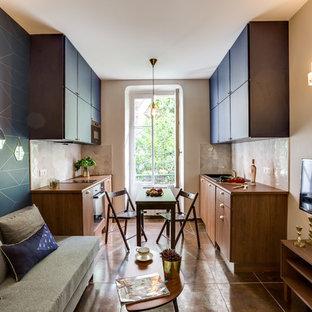 Cette image montre une petit cuisine ouverte parallèle design avec un évier encastré, un placard à porte affleurante, des portes de placard noires, une crédence blanche, une crédence en carreau de céramique et un électroménager noir.