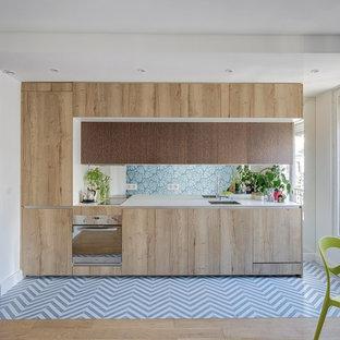 パリの小さいコンテンポラリースタイルのおしゃれなキッチン (一体型シンク、中間色木目調キャビネット、珪岩カウンター、ミラータイルのキッチンパネル、シルバーの調理設備、セメントタイルの床、アイランドなし、青い床、白いキッチンカウンター、フラットパネル扉のキャビネット、メタリックのキッチンパネル) の写真