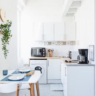 Cette image montre une petite cuisine américaine marine en L avec un évier posé, un placard à porte plane, des portes de placard blanches, une crédence multicolore, un sol gris et béton au sol.