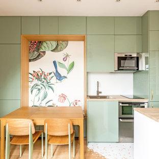 Idée de décoration pour une cuisine ouverte linéaire style shabby chic de taille moyenne avec un évier encastré, un placard à porte affleurante, des portes de placards vertess, un plan de travail en stratifié, une crédence blanche, une crédence en mosaïque, un électroménager en acier inoxydable, un sol en bois clair, un îlot central, un sol marron et un plan de travail marron.