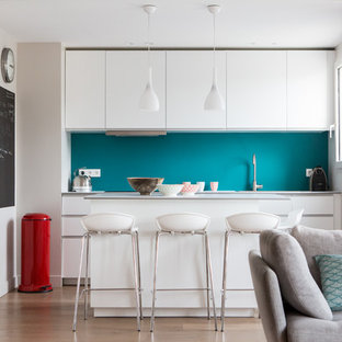 Inspiration for a mid-sized contemporary single-wall open plan kitchen in Paris with flat-panel cabinets, white cabinets, blue splashback, light hardwood floors and with island.