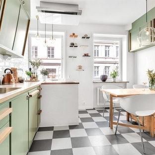 ストックホルムのミッドセンチュリースタイルのおしゃれなキッチン (ドロップインシンク、フラットパネル扉のキャビネット、緑のキャビネット、木材カウンター、白いキッチンパネル、サブウェイタイルのキッチンパネル、パネルと同色の調理設備、アイランドなし、マルチカラーの床、ベージュのキッチンカウンター) の写真