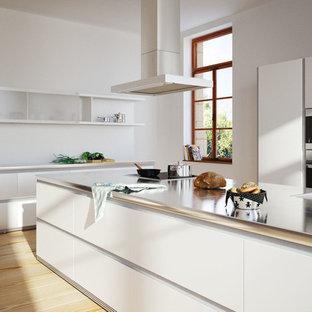Inspiration pour une cuisine parallèle minimaliste avec un évier encastré, un placard à porte plane, des portes de placard blanches, un électroménager noir, un sol en bois clair, 2 îlots et un sol orange.