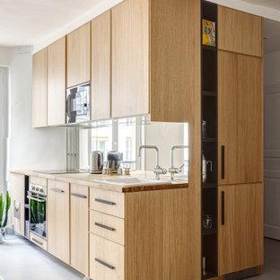 Diseño de cocina en L, contemporánea, pequeña, sin isla, con fregadero encastrado, armarios con paneles lisos, puertas de armario de madera clara, encimera de madera, salpicadero con efecto espejo, electrodomésticos con paneles, suelo de baldosas de porcelana, suelo gris y encimeras beige