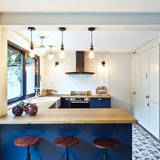 Cette photo montre une cuisine chic en U de taille moyenne avec un plan de travail en bois, une crédence blanche, un électroménager en acier inoxydable, un sol en carreaux de ciment, un évier de ferme, un placard à porte shaker, des portes de placard bleues, une péninsule, un sol multicolore et un plan de travail beige.