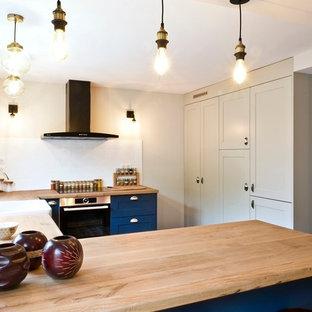 Offene, Mittelgroße Klassische Küche ohne Insel in U-Form mit Einbauwaschbecken, Arbeitsplatte aus Holz, Küchenrückwand in Weiß, Rückwand aus Porzellanfliesen, Küchengeräten aus Edelstahl, Zementfliesen, grauem Boden und gelber Arbeitsplatte in Paris