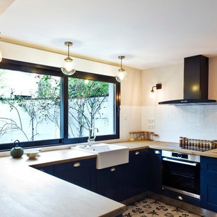 Photo of a medium sized traditional u-shaped open plan kitchen in Paris with a built-in sink, wood worktops, white splashback, porcelain splashback, stainless steel appliances, cement flooring, no island, grey floors and yellow worktops.