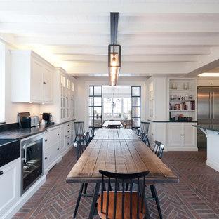 Geräumige Country Wohnküche in L-Form mit Landhausspüle, Schrankfronten im Shaker-Stil, weißen Schränken, Küchengeräten aus Edelstahl, Backsteinboden und Kücheninsel in Sonstige