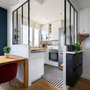 Inspiration for a small contemporary u-shaped separate kitchen in Paris with a single-bowl sink, white cabinets, wood benchtops, white splashback, stainless steel appliances, ceramic floors, no island, brown benchtop, flat-panel cabinets and multi-coloured floor.