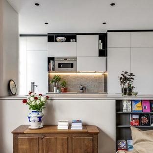 Modelo de cocina de galera, ecléctica, grande, abierta, con puertas de armario blancas, salpicadero verde, salpicadero de azulejos de terracota, electrodomésticos con paneles y península