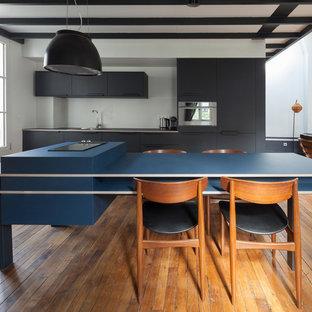 Cette image montre une cuisine ouverte linéaire nordique avec un placard à porte plane, des portes de placard noires, un électroménager en acier inoxydable, un sol en bois brun, un îlot central, un évier encastré, un plan de travail bleu, une crédence blanche et un sol marron.