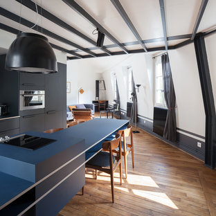 Scandinavian open concept kitchen ideas - Danish single-wall medium tone wood floor and brown floor open concept kitchen photo in Paris with an undermount sink, flat-panel cabinets, black cabinets, white backsplash, stainless steel appliances, an island and blue countertops