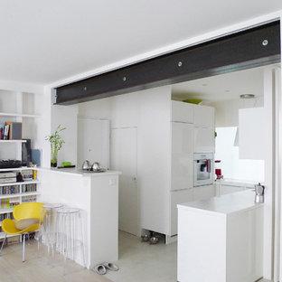 Cette image montre une cuisine ouverte design en L de taille moyenne avec des portes de placard blanches, un sol en bois clair et une péninsule.