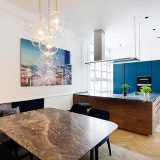 Idées déco pour une cuisine américaine contemporaine avec un placard à porte plane, des portes de placard bleues, un îlot central et un sol multicolore.