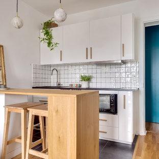 Idée de décoration pour une petit cuisine nordique avec un placard à porte plane, des portes de placard blanches, une crédence blanche, une péninsule, un sol gris et un plan de travail gris.