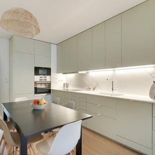 Aménagement d'une cuisine américaine scandinave avec un évier 1 bac, un placard à porte plane, des portes de placard grises, une crédence blanche, une crédence en marbre, un sol en bois clair, un sol beige et un plan de travail blanc.