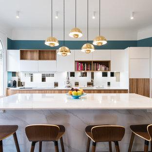 Idéer för stora funkis vitt kök, med en dubbel diskho, släta luckor, vita skåp, vitt stänkskydd, rostfria vitvaror, en köksö, ljust trägolv och vitt golv
