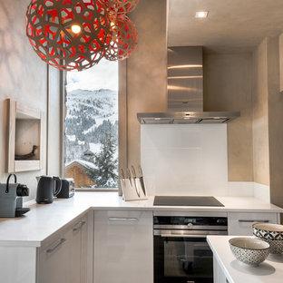 Exemple d'une cuisine tendance en L fermée et de taille moyenne avec des portes de placard blanches, une crédence blanche, une crédence en feuille de verre, un électroménager en acier inoxydable et un îlot central.