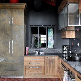 Design ideas for an eclectic l-shaped eat-in kitchen in Other with flat-panel cabinets, medium wood cabinets, black splashback, stainless steel appliances, no island and red floor.