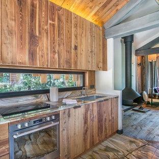 Diseño de cocina lineal, rústica, de tamaño medio, abierta, sin isla, con fregadero bajoencimera, encimera de madera, electrodomésticos con paneles y suelo de madera en tonos medios
