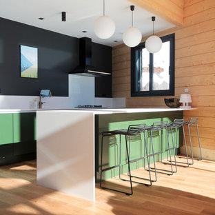 Idée de décoration pour une cuisine ouverte parallèle chalet de taille moyenne avec un placard à porte plane, des portes de placards vertess, un plan de travail en surface solide, une crédence blanche, un sol en bois clair, un plan de travail blanc, une crédence en feuille de verre et une péninsule.