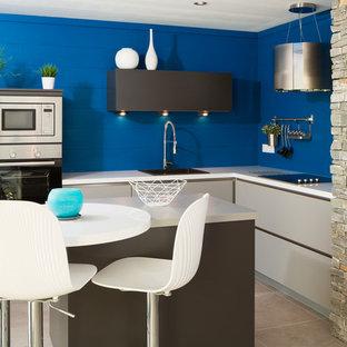 Diseño de cocina comedor en L, contemporánea, pequeña, con fregadero integrado, puertas de armario blancas, encimera de acero inoxidable, salpicadero azul y una isla