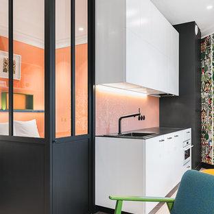 Diseño de cocina lineal, actual, abierta, con fregadero encastrado, armarios con paneles lisos, puertas de armario blancas, salpicadero rosa, salpicadero de vidrio templado, electrodomésticos blancos, suelo de madera clara, suelo beige y encimeras negras