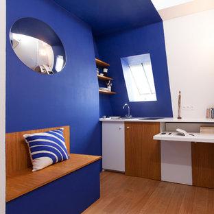 Aménagement d'une petite cuisine ouverte linéaire contemporaine avec un évier posé, des portes de placard blanches, un sol en bois brun et aucun îlot.