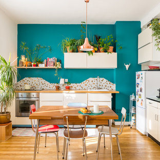 Midcentury l-shaped eat-in kitchen in Lyon with a drop-in sink, flat-panel cabinets, white cabinets, wood benchtops, multi-coloured splashback, mosaic tile splashback, stainless steel appliances, medium hardwood floors and no island.