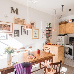 Aménagement d'une cuisine américaine éclectique avec un placard à porte plane, des portes de placard en bois clair, un plan de travail en bois, un électroménager blanc, une péninsule et un sol beige.