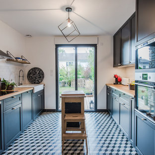 Photo of a scandinavian galley separate kitchen in Montpellier with a farmhouse sink, recessed-panel cabinets, black cabinets, wood benchtops, white splashback, subway tile splashback, stainless steel appliances, with island, multi-coloured floor and beige benchtop.