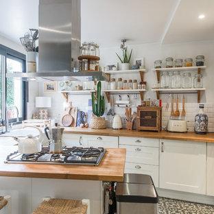パリのエクレクティックスタイルのおしゃれなキッチン (エプロンフロントシンク、シェーカースタイル扉のキャビネット、白いキャビネット、木材カウンター、白いキッチンパネル、サブウェイタイルのキッチンパネル、シルバーの調理設備、グレーの床) の写真