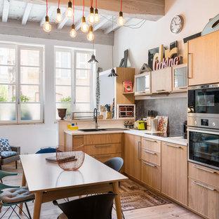 Exemple d'une cuisine américaine éclectique en L avec un évier posé, un placard à porte plane, des portes de placard en bois brun, une crédence noire, un électroménager noir, un sol en bois clair, aucun îlot et un sol beige.