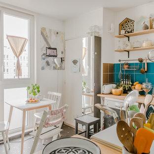Inspiration pour une cuisine américaine bohème en L avec un évier 2 bacs, un placard sans porte, un plan de travail en bois, une crédence bleue, aucun îlot, un sol multicolore et un plan de travail beige.