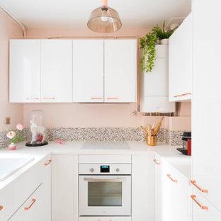 Exemple d'une petite cuisine tendance fermée avec un évier 1 bac, un placard à porte plane, des portes de placard blanches, une crédence rose, un électroménager encastrable, aucun îlot, un sol beige et un plan de travail blanc.